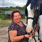 woman stroking black and white horse