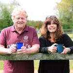 man and woman holding cups of tea